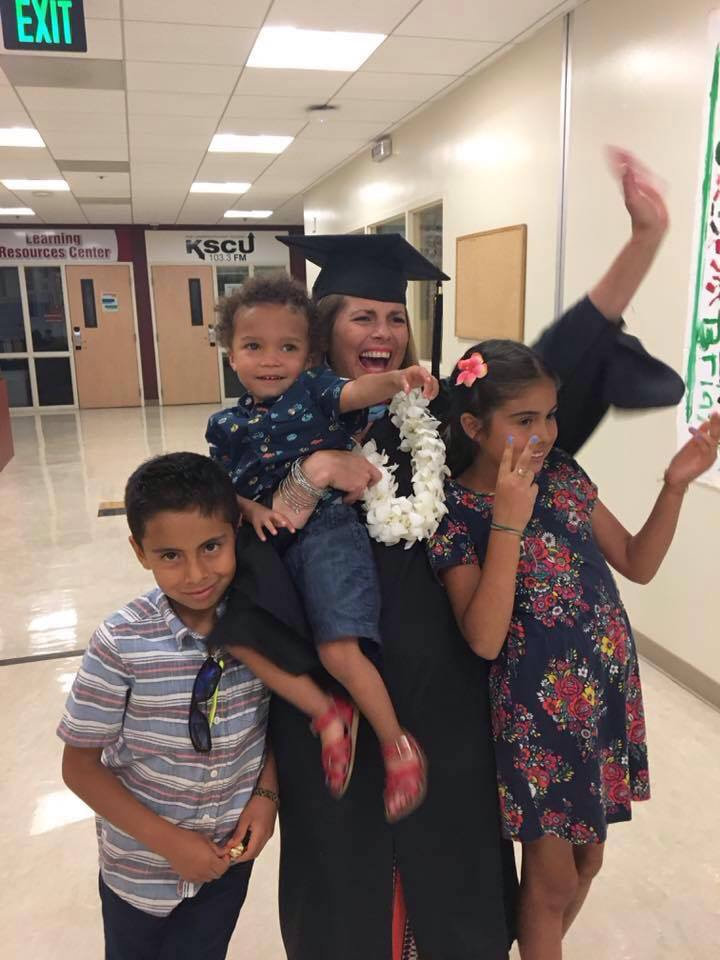 Spanish teacher Aimee Verapinto graduating from her Master's program at Santa Clara University. She is standing with her two children, Matias (left) and Savanna (right), and holding her nephew, Gabriel.