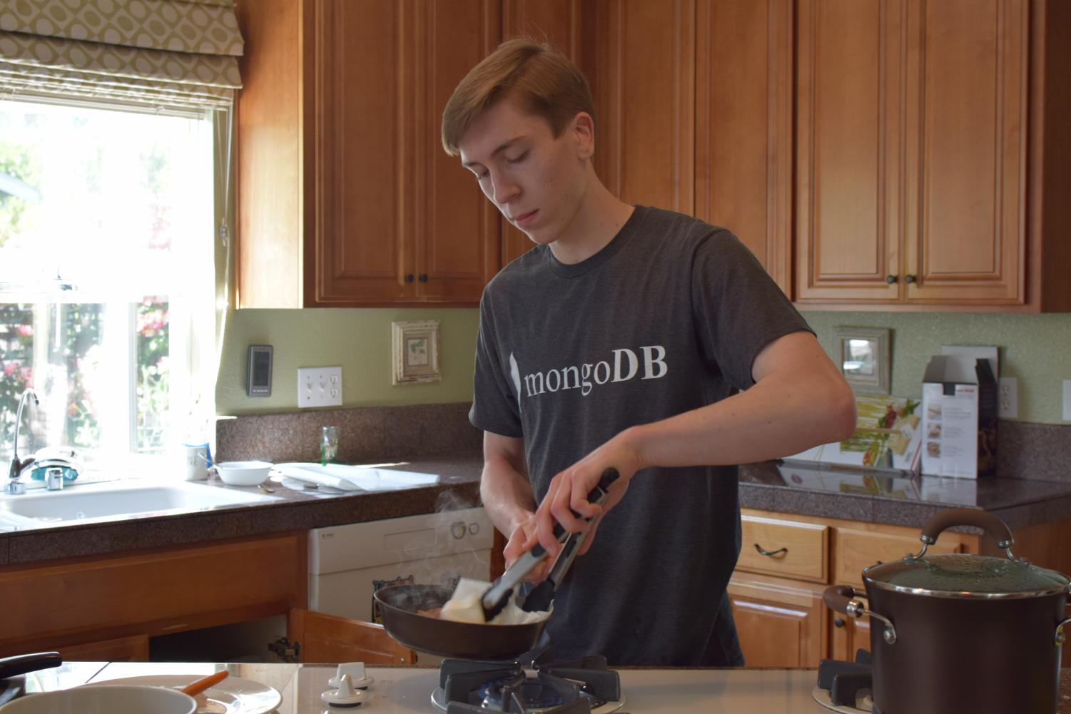 Thomas Kamm (12) cooks the beef slices in a pan, an ingredient to create the sauce. Due to excess oils, Kamm wipes the pan with a paper towel.