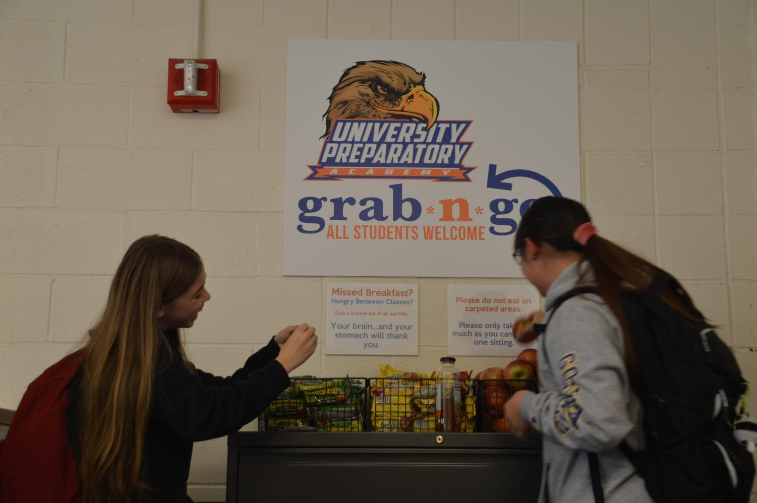 This photo illustration depicts, from left to right, eighth grader Chelsea Nguyen laughing while opening a granola bar and eighth grader Jasmine Dang picking up an apple. Nguyen has taken apples and oranges from Grab-n-Go while Dang has taken milk and apples.