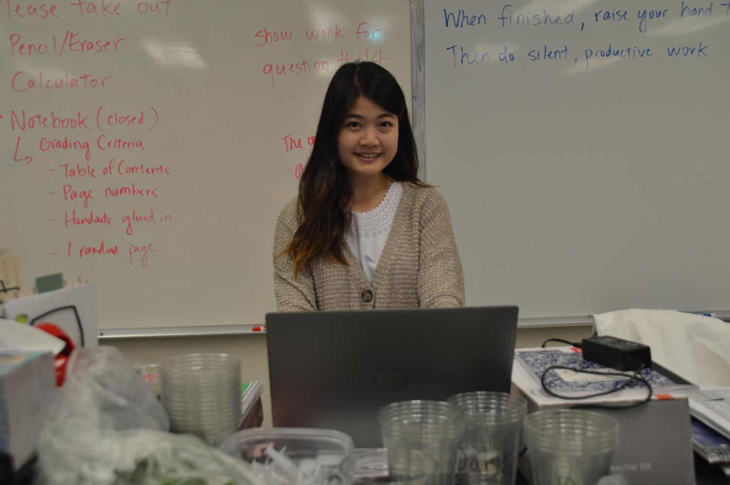 Science teacher Vivien Chern smiles at the front desk in the classroom where she teaches AP Biology, Cal.