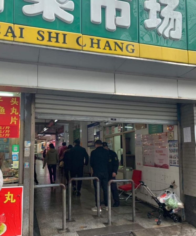 Sanitation officers are stationed at the doorway to a vegetable market in Shanghai, China. Courtesy of Wang Xiu Ying (name changed)
