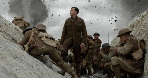George MacKay stands as Lance Corporal Schofield in a World War I trench.